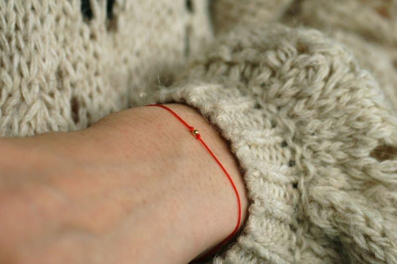Bransoletka wiązana na czerwonym sznurku na szczęście z jedną kuleczką